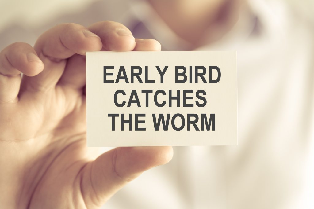 Closeup on businessman holding a card with text EARLY BIRD CATCHES THE WORM, business concept image with soft focus background and vintage tone