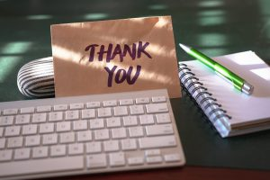 Thank you note and keyboard on desk