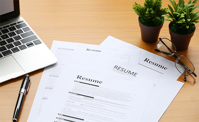 resume and laptop on desk
